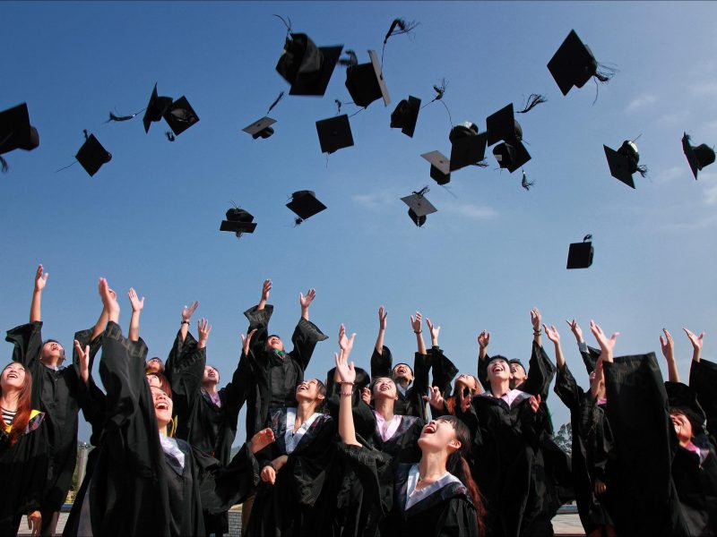Canva - Newly Graduated People Wearing Black Academy Gowns Throwing Hats Up in the Air