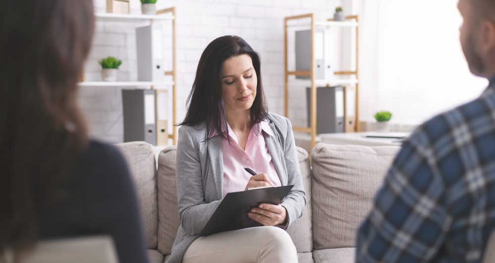Family therapy. Professional psychologist taking notes at couple meeting with patients